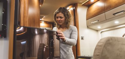 Girl opening a fridge in a luxury motorhome