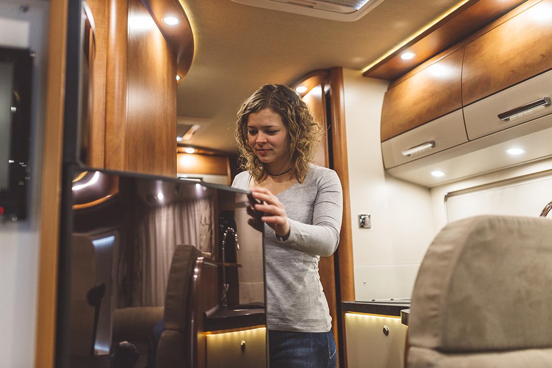 Girl opening a fridge in a luxury motorhome