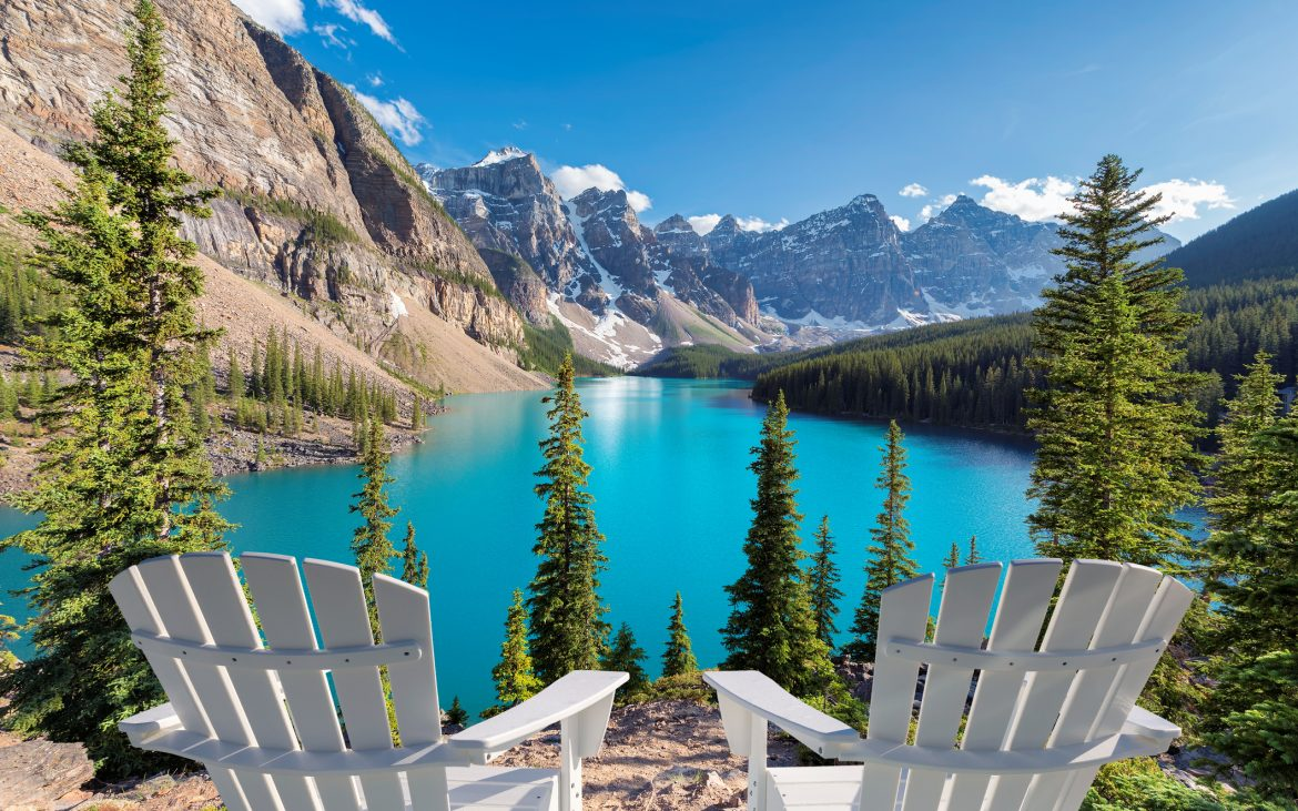 Two chairs near beautiful turquoise waters of the Moraine Lake at sunset with snow-covered peaks above it in Rocky Mountains, Banff National Park