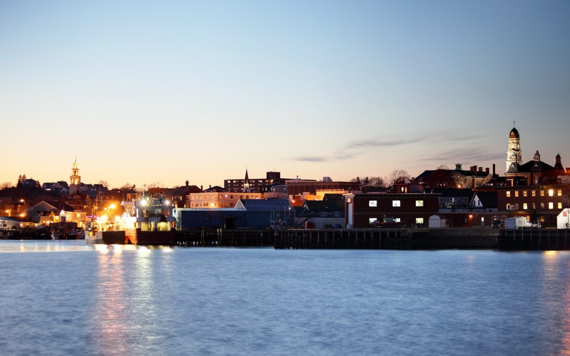 Massachusetts coastal town of Gloucester at dusk, buildings along harbor