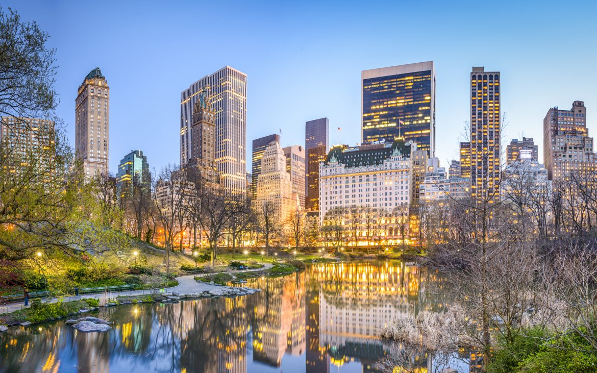 Manhattan cityscape from the Lagoon in Central Park, buildings reflections in water at dusk