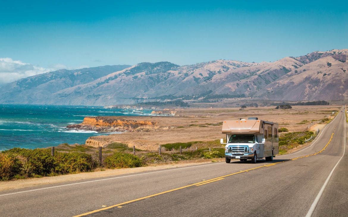 RV driving down PCH near ocean on sunny day