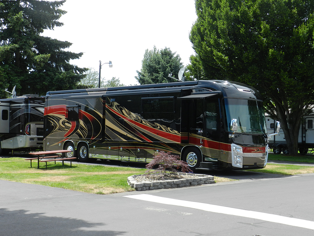 A motorhome with exterior painting parked amid lush landscaping.