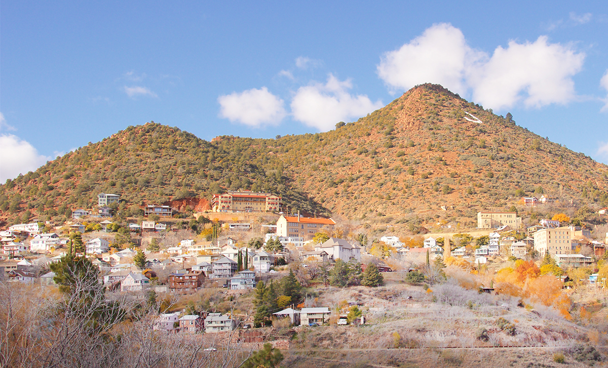 Buildings stand on a desert mountainside.