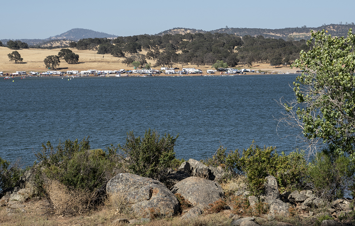 A view from the opposite bank of an RV park nestled on the shores of a lake.