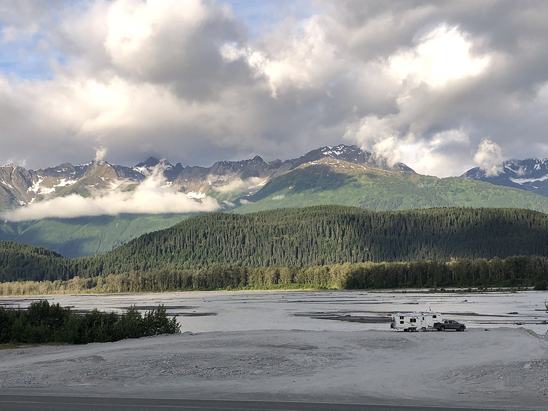 An RV in a vast wilderness landscape with forested hills and snowcapped mountains in the background.