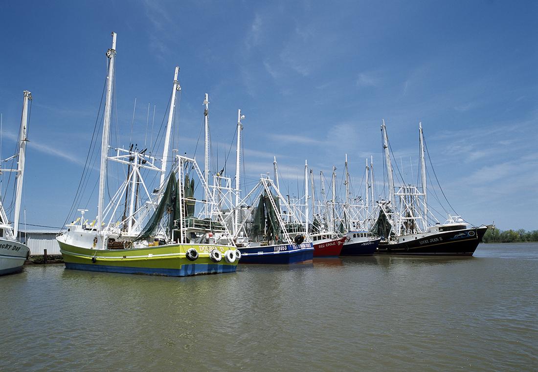 Shrimp boat at dock under a blue sky.