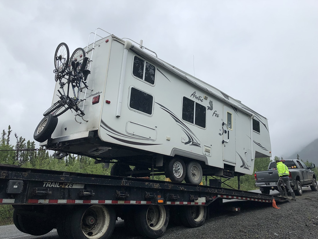 An RV on a trailer after repairs.