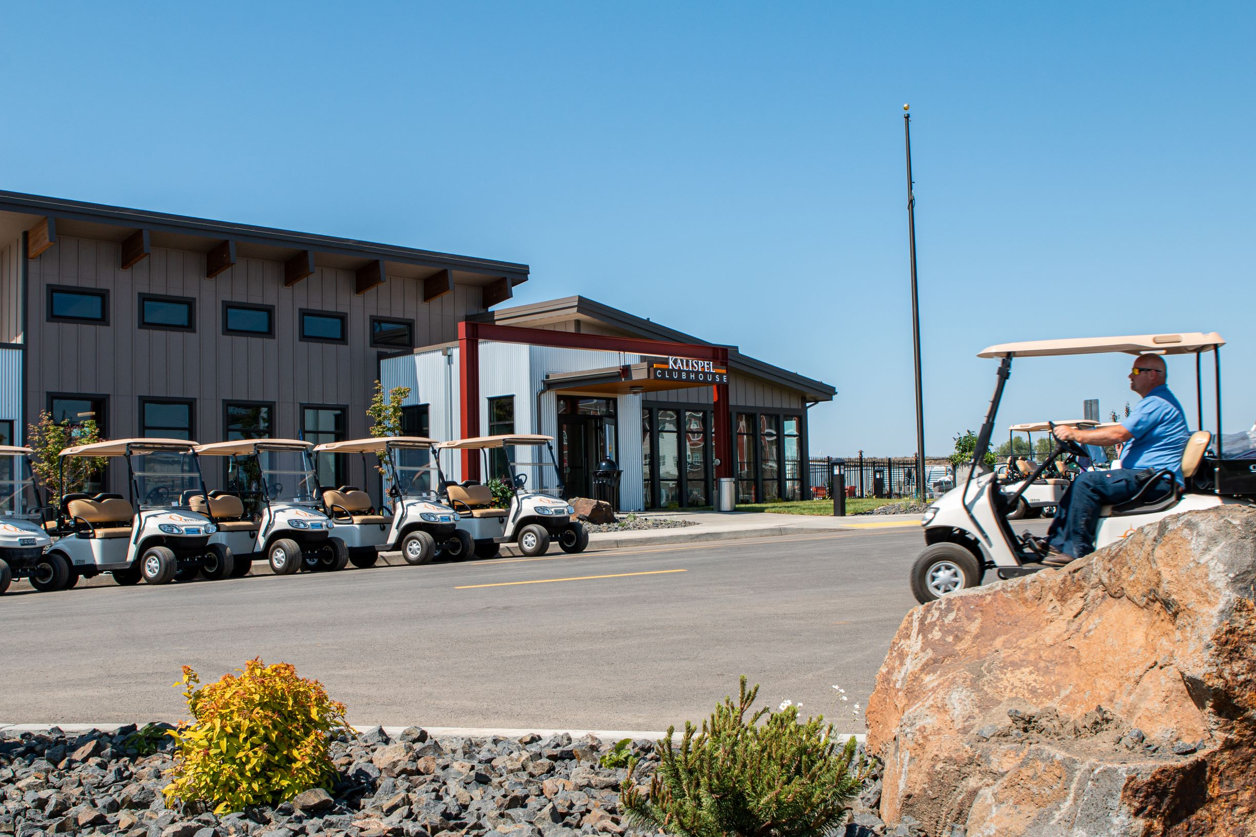 A line of golf cars parked in front of a Northern Quest building.