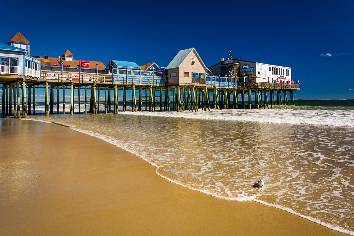 A pier laden with colorful buildings juts out into the ocean.