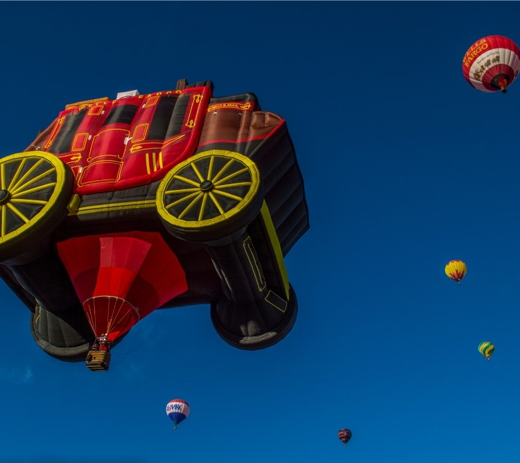 A balloon in the stage of a Wells Fargo stagecoach takes to the skies.