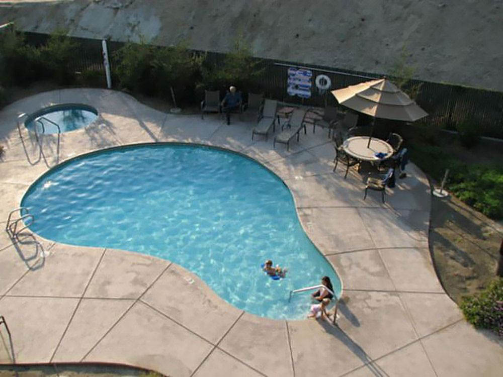 Aerial shot of bathers relaxing in a pear-shaped pool with hot top.