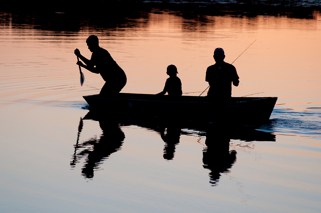 Silhouette of families on boat fishing.