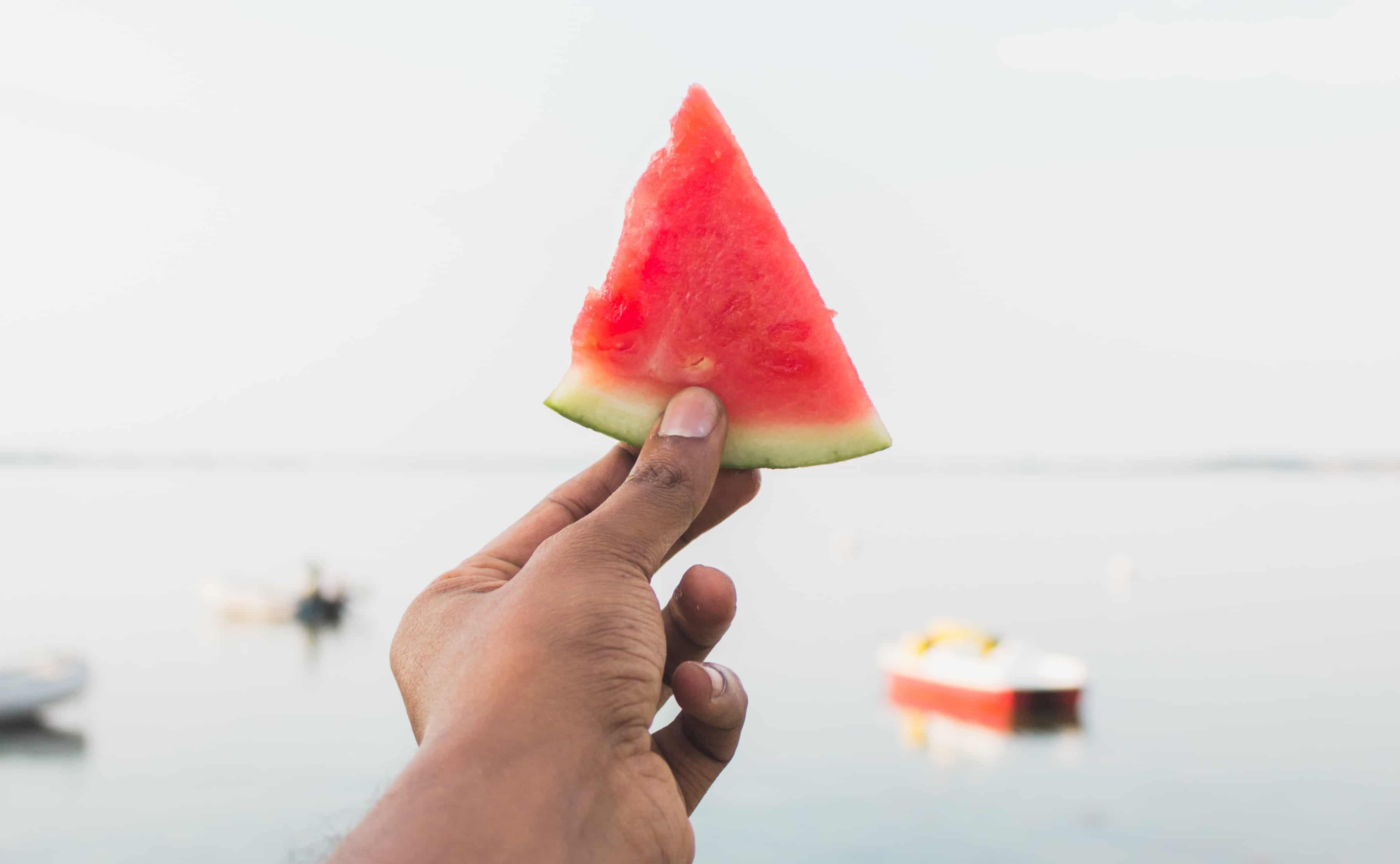A hand holds up a triangular slice of seedless watermelon in front of a red boat.