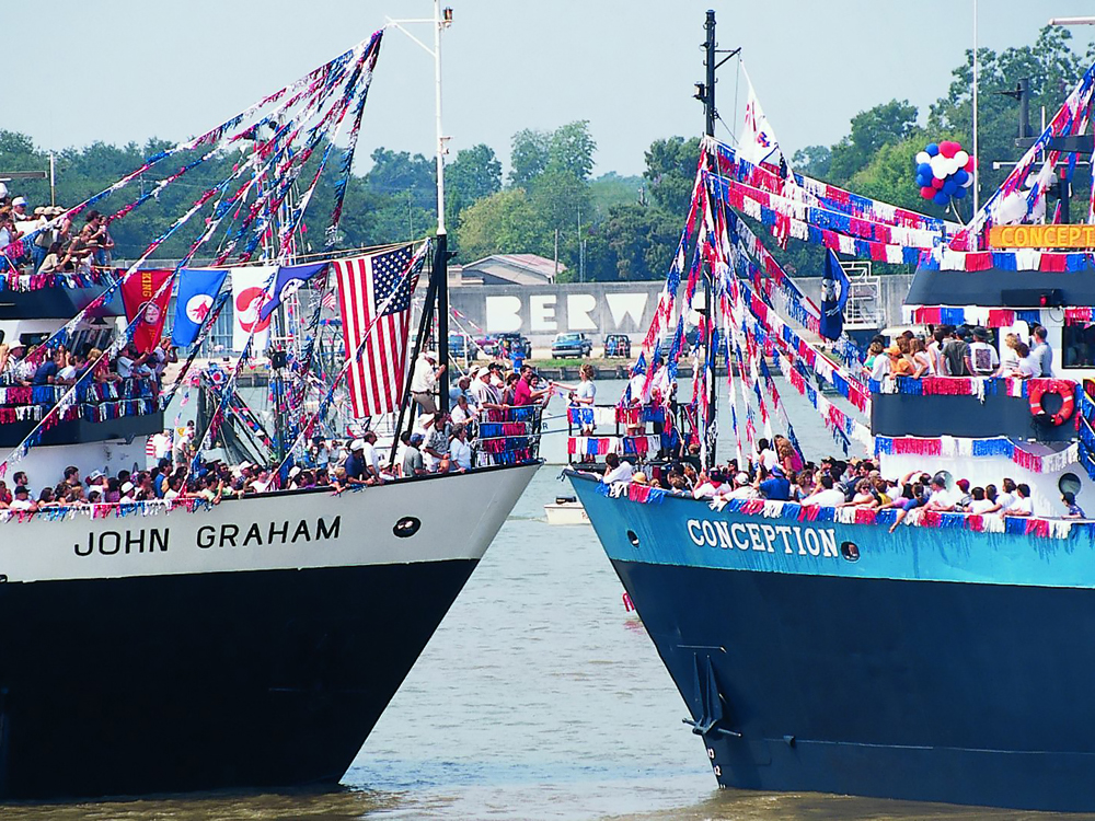 Two ships with patriotic banners and crowds on deck meet bow to bow.