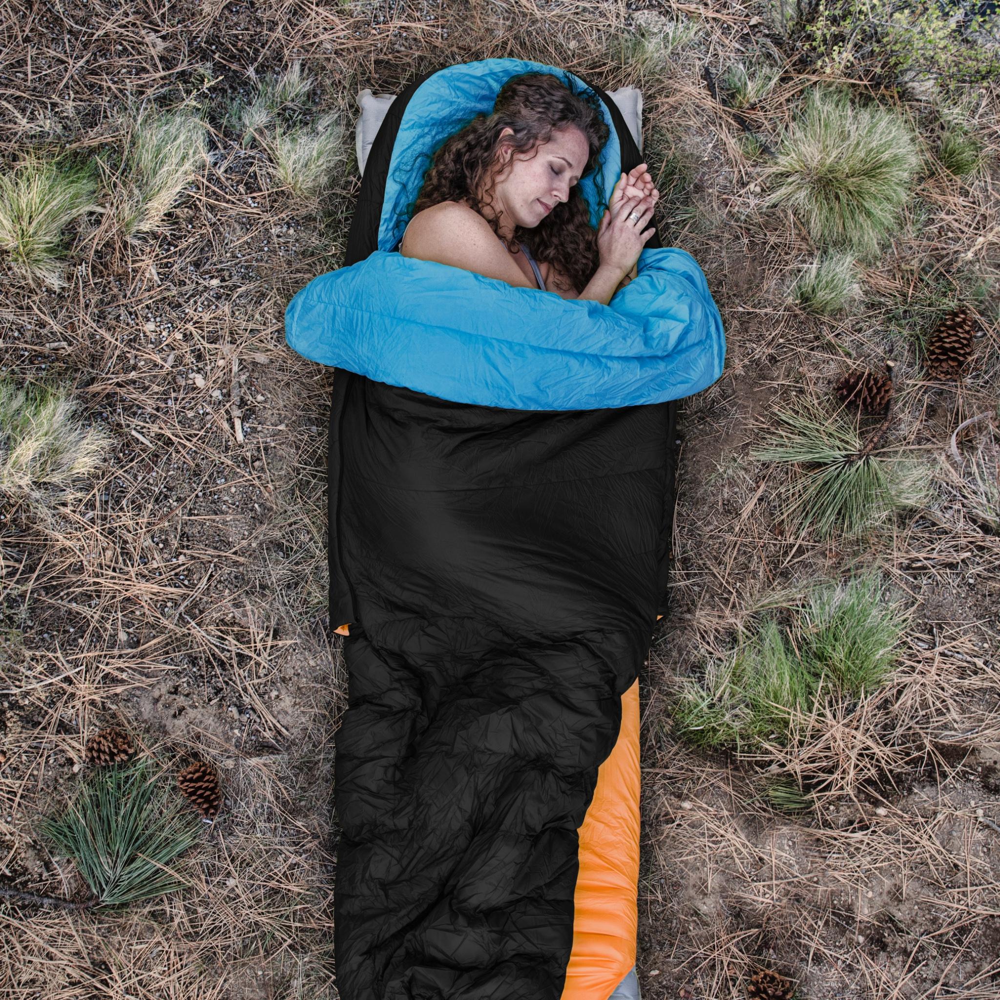Woman sleeping outside on side in sleeping bag