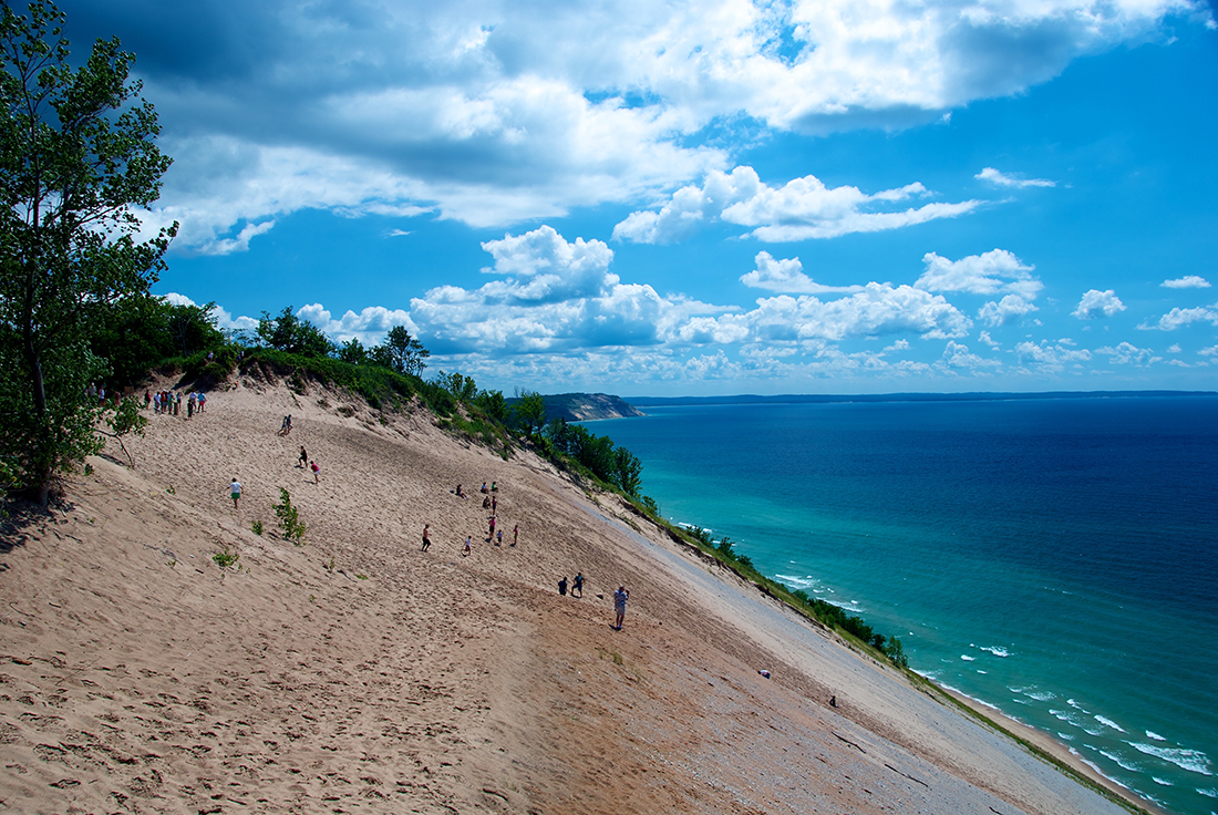 People walk on a massive sand dune that slopes down to blue waters of Lake Michigan.