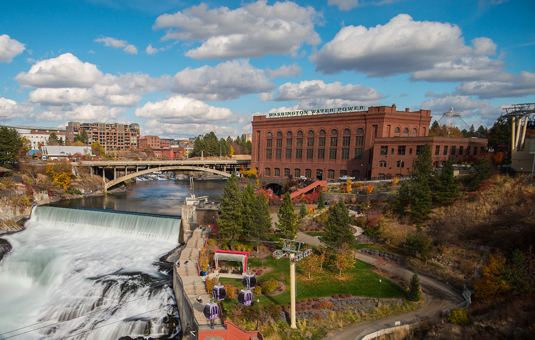 A river cascades over a waterfall crossed by a bridge and flanked by mid-20th-century buildings.