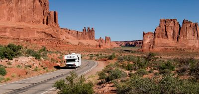 A Class C motorhome driving through Arches National Park in Utah.