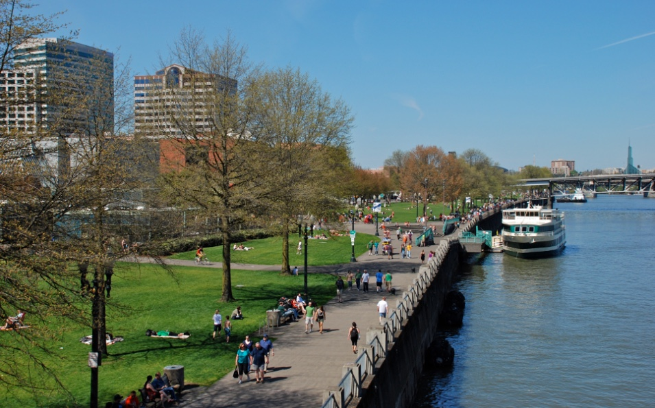 Walkers and joggers move on a riverwalk alongside a wide river with boats.