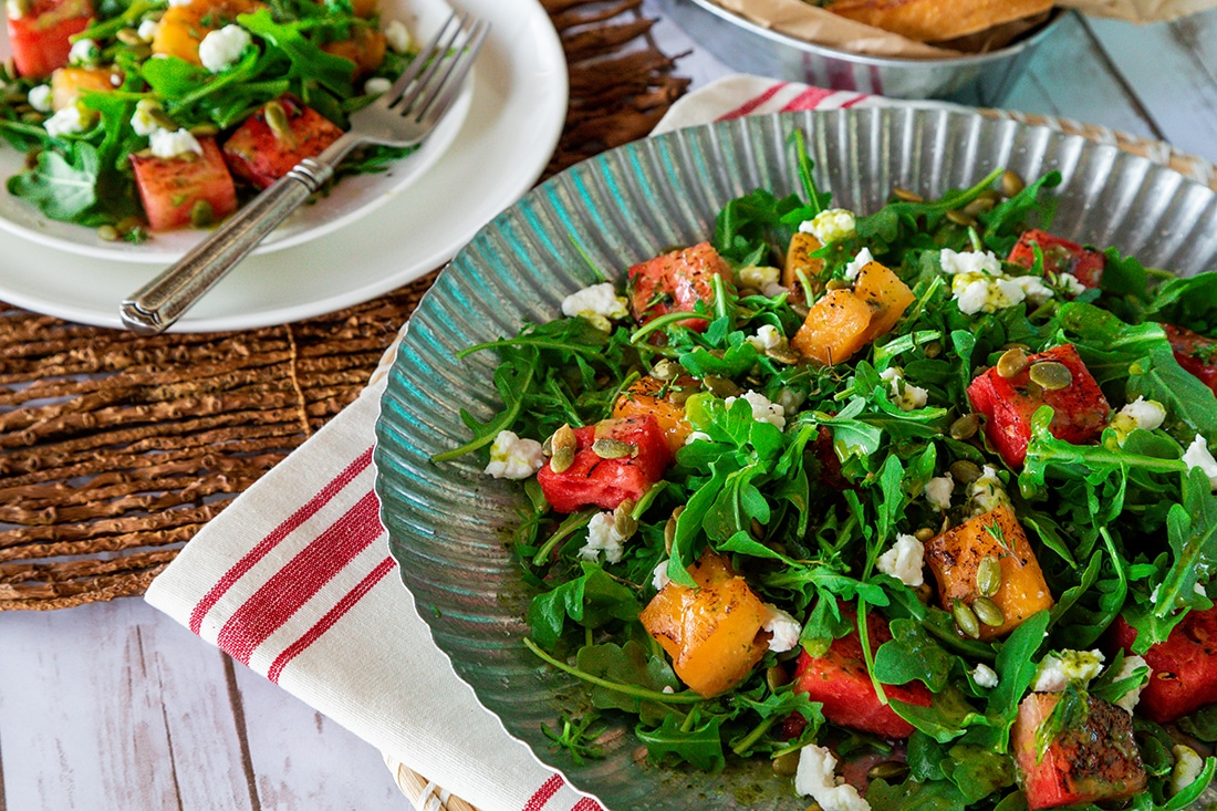 A bowl of salad with goat cheese, greens and cubed slices of watermelon.