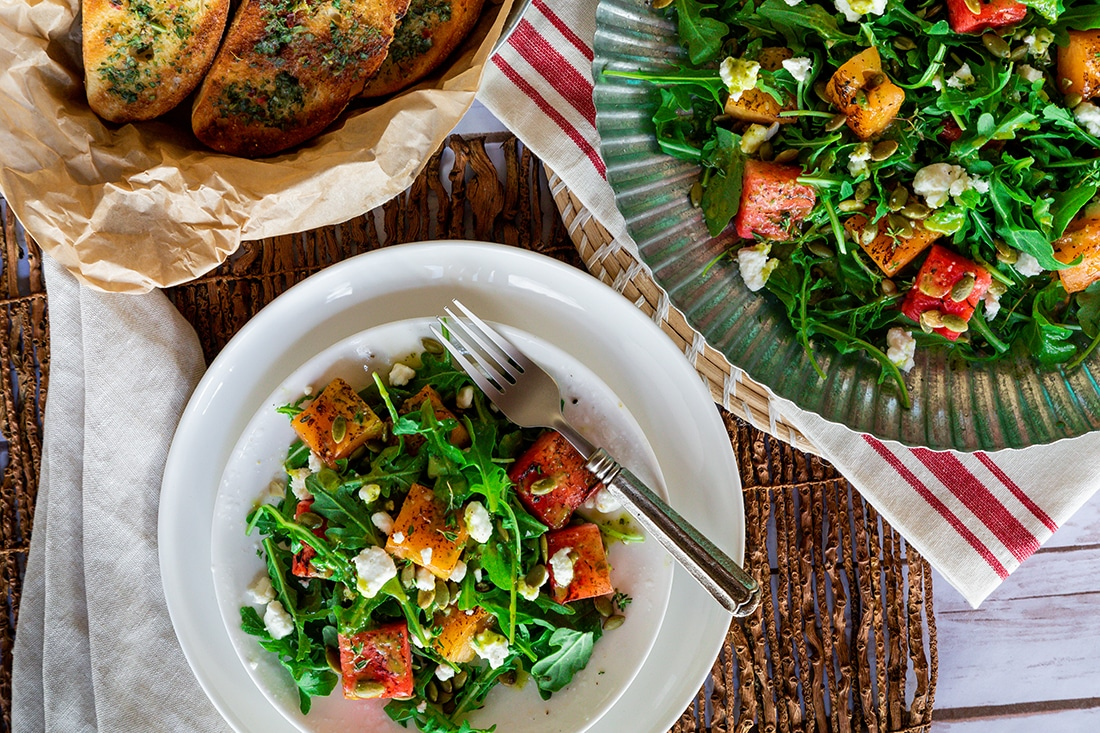 Watermelon salad with greens and goat cheese in a bowl and on a plate with garlic bread on the side.