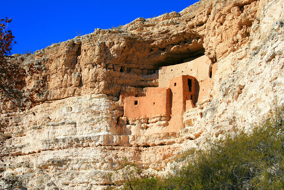 A pueblo structure built into a cliffside looms over a valley.