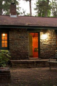 A welcoming cabin emates golden light in the forest dusk.