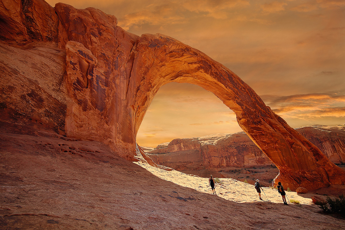 A rock arch towers over three hikers on a arid Utah landscape.