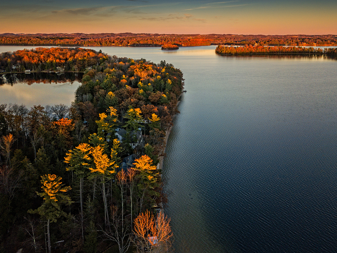 Islands dappled golden foliage sit on calm waters in Michigan.