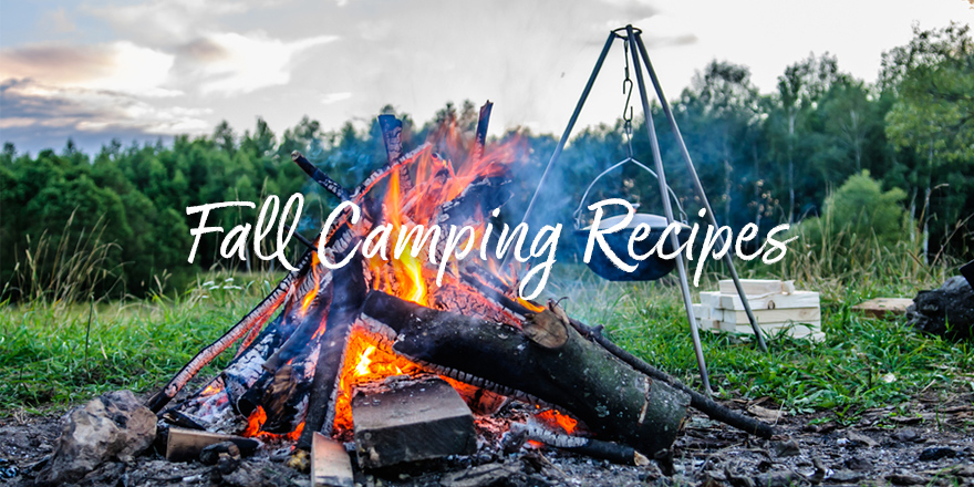 Flames roar in a tepee fire with camping tripod in the background, fall camping recipes.