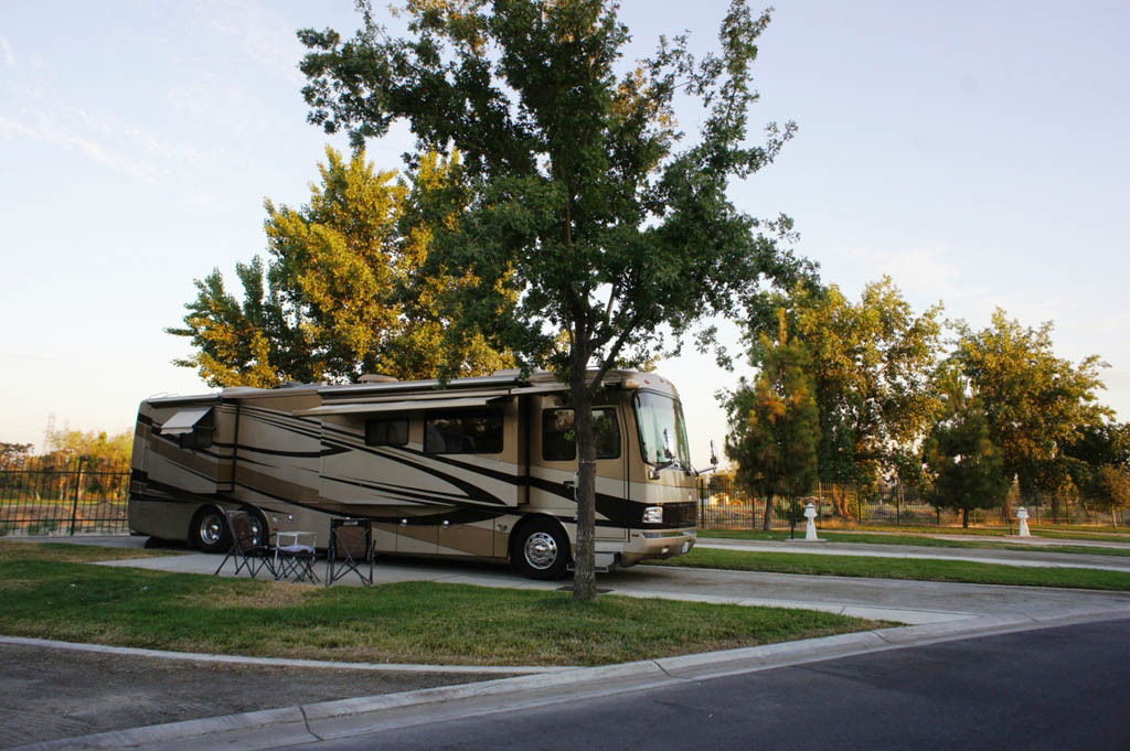 Brown and tan colored motorhome parked in driveway near trees on sunny day