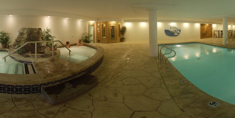 A sauna with indoor pool and flagstone flooring.