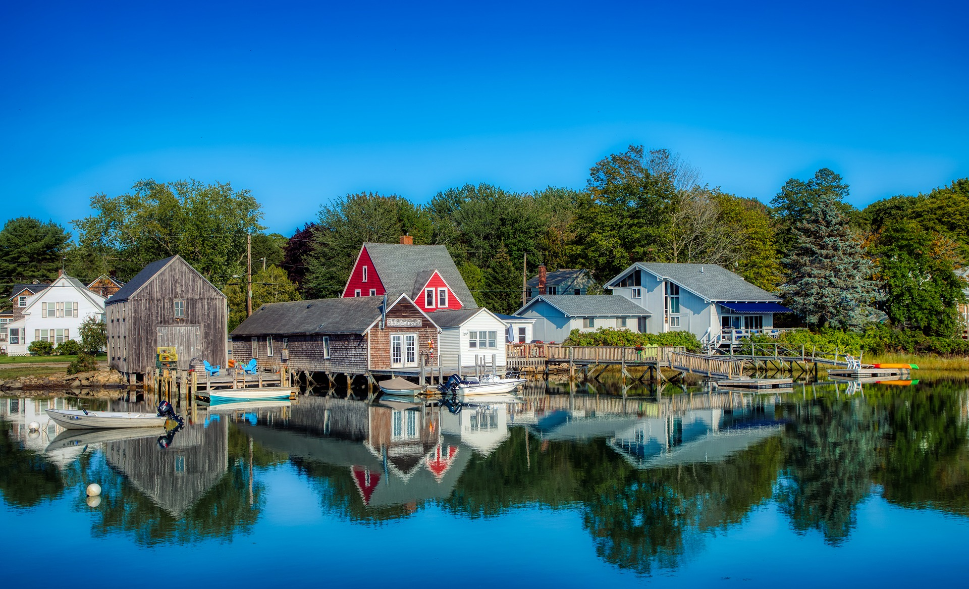 Small houses — including a red, gabled house — reflected on the water.