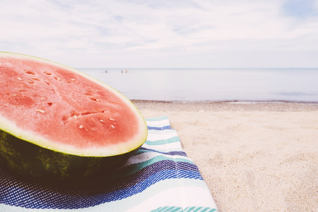 The end of a melon rests on a towel at the beach.