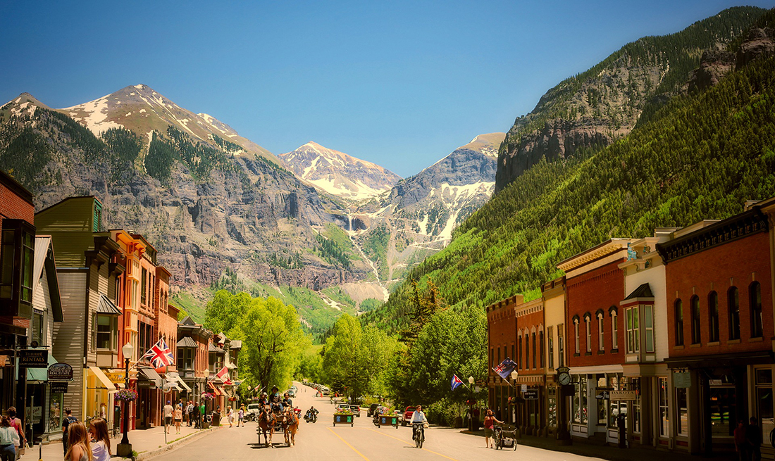 A street lined with Old West-style buildings on each side as mountains loom in the background.