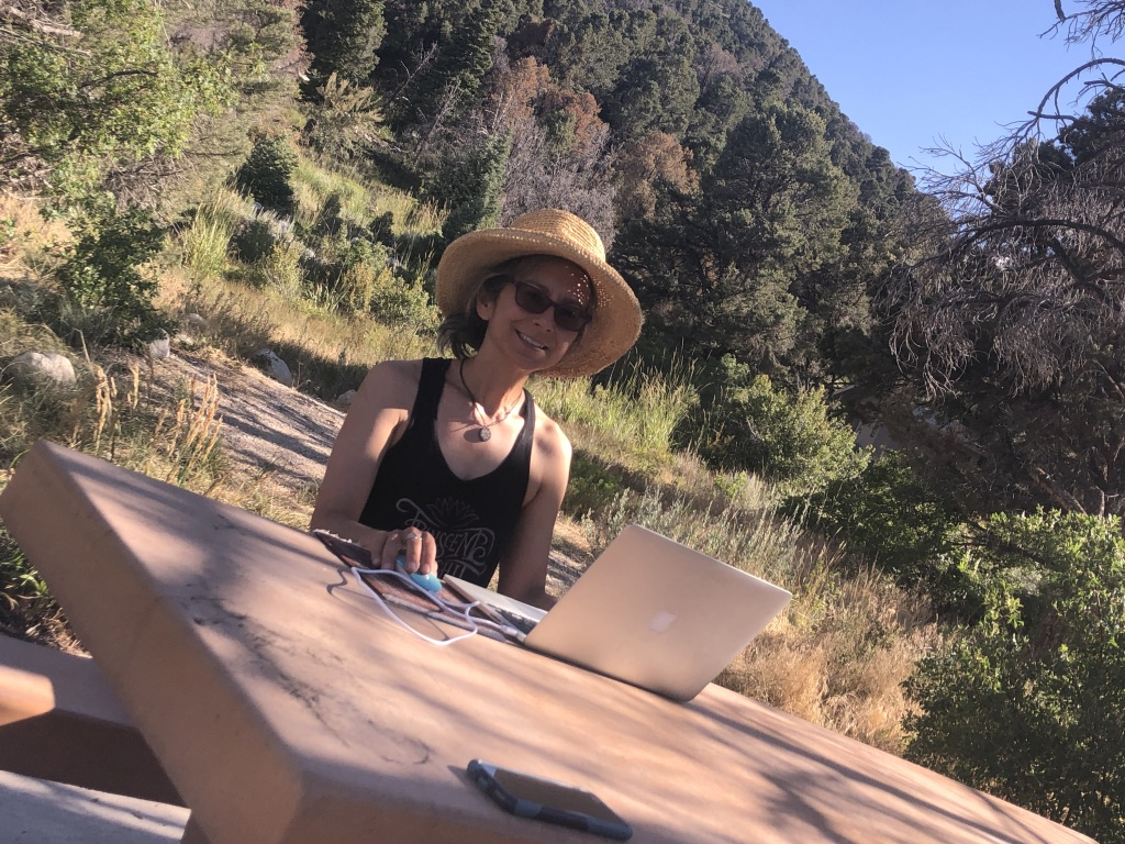 A woman sitting at a campground table with a laptop computer and wearing a hat.