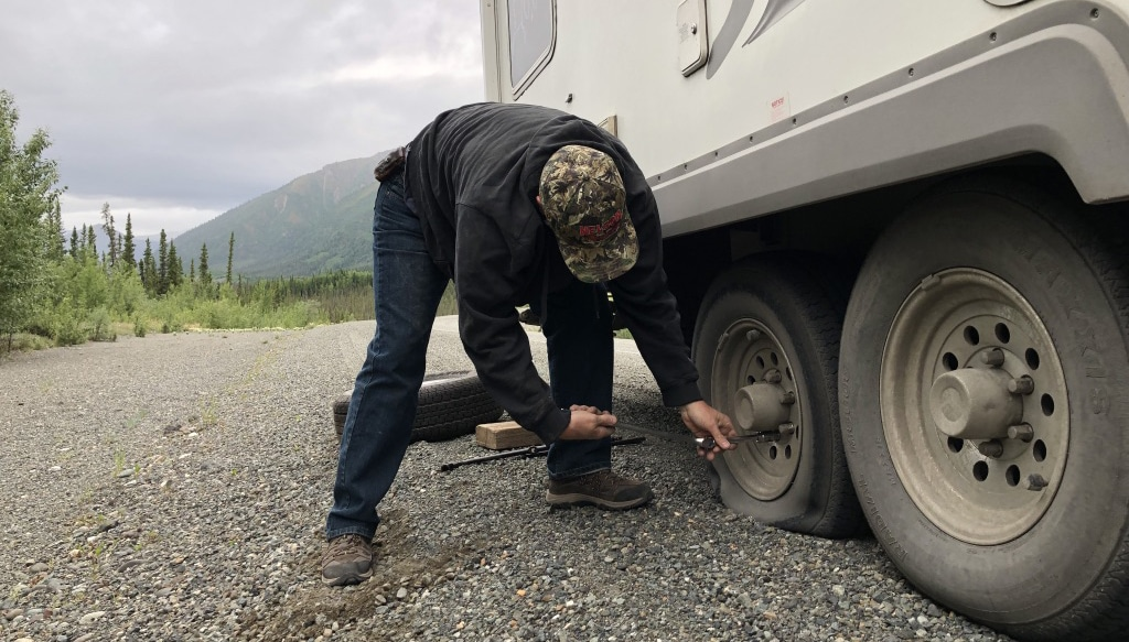 A man changes one of the tires of a tag-axle fifth-wheel.