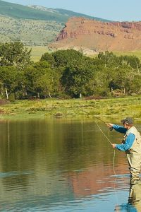An angler with beige waders and a fishing vests casts a line in a lake as hills gently rise in the horizon.