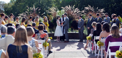 A couple getting married outdoors as guests look on amid plants and trees.