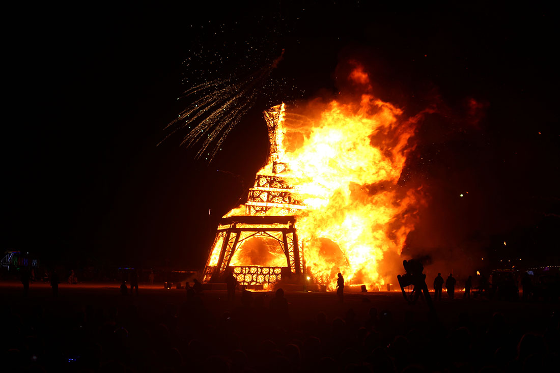 Giant statue of a man blazes in flames.