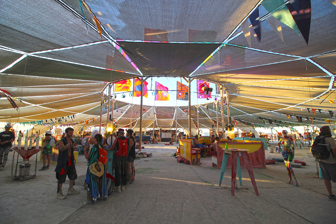 Colorfully dressed event-goers gather under a circular shaped canopy.