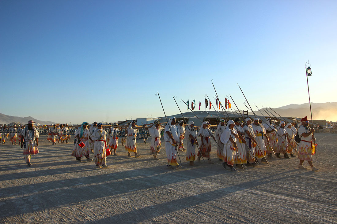 Festival-goers dressed in robed adorned with flame patterns march in formation.