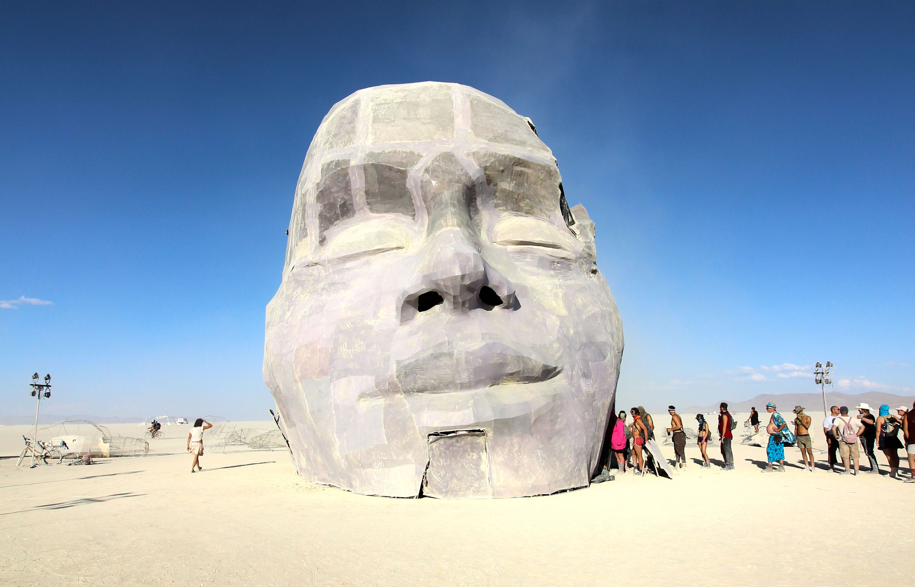 A column of people walk into the sculpture of a 20-foot-tall head that wears a peaceful expression.