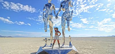 A woman in futuristic garb flanked by two reflctive statues.