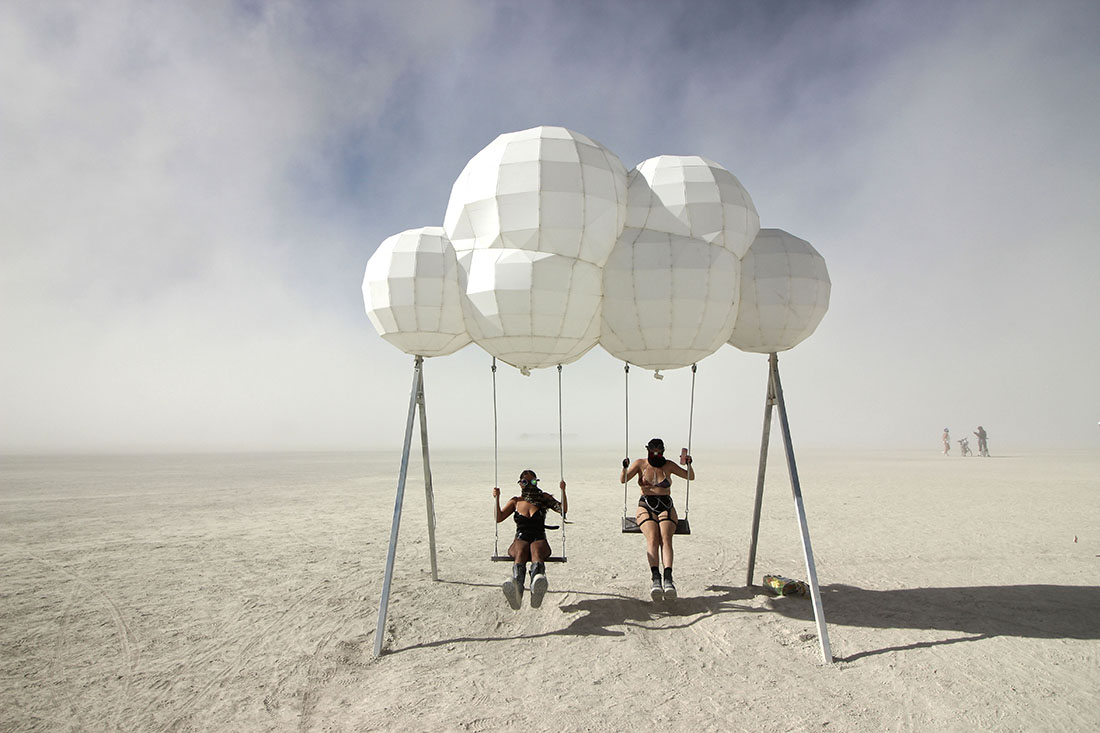 Two women dressed an apocalyptic gear play on futuristic a swing set.