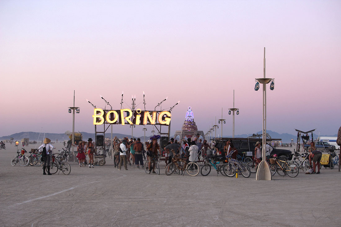 A giant lighted sign hangs over a gathering of bicycle riders and individuals.