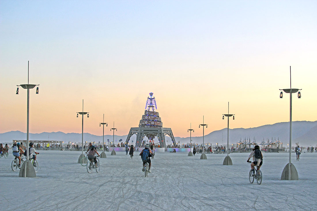 Burning man attendees cycle toward a giant statue of the Burning Man himself.