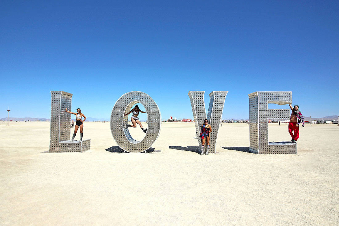 """Four colorfully dressed people pose with a giant """"love"""" sculpture."""