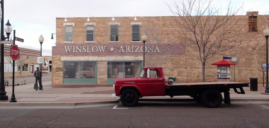 Old red truck parked outside brick building